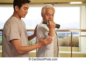 asian old man exercising using dumbbell in rehab center