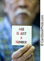 Asian Old man shows his card with AGE IS JUST A NUMBER Text