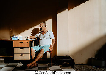 Asian old man sitting on the chair