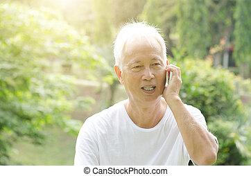 Asian old man talking on phone