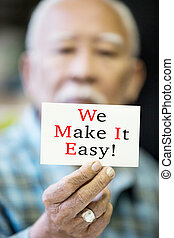 Asian Old man with WE MAKE IT EASY! message on hand