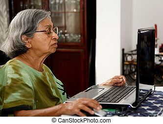 Asian old woman using computer - Elderly Asian Indian woman...