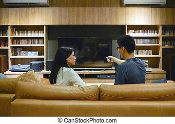 asian para, używając, niejaki, zdalne sterowanie, żeby obrócić się, na, telewizja, z, okienko osłaniają