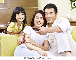 asian parents and daughter watching TV at home