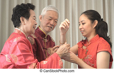 Asian parents give daughter in law gold bracket Chinese New Year