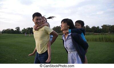 Asian parents giving children piggyback ride in park