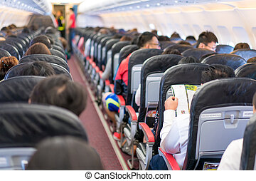Asian passenger reading the magazine / menue / catalog while waiting for plane take of inflight.