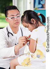Asian pediatrician examining little girl