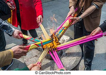 asian people burning incense for praying