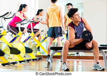 Asian people exercising sport for fitness in gym - Chinese...