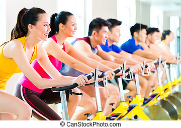 Chinese Asian sport group of men and women in fitness club or gym exercising on spinning bikes