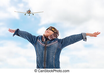 Asian pilot boy with Propeller plane with blue sky.