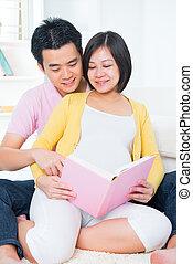 Asian pregnant couple reading book