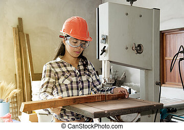 Asian pretty female carpenter Using Electric Sander for wood