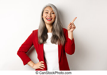 Asian professional businesswoman showing logo, smiling and pointing finger upper right corner, standing over white background