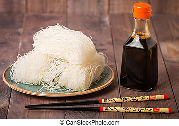 Asian raw glass noodles, chopsticks and soy sauce on wooden...