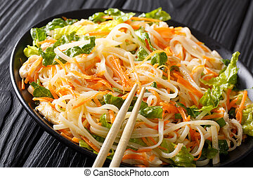 Asian salad with rice noodles, chicken, carrot and greens ...