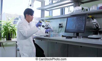Asian scientist working in lab. Doctor making microbiology ...