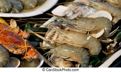 Asian Seafood, shrimps, crawfish, crabs on the counter in...