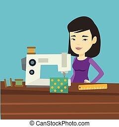 Seamstress using sewing machine at workshop. - Asian...