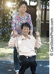 Asian senior adult women playing swing at outdoor playground
