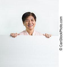 Asian senior citizen holding blank white board