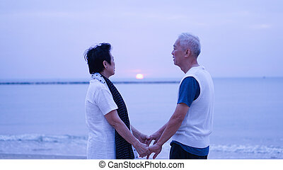 Asian senior couple dating at sunrise sea