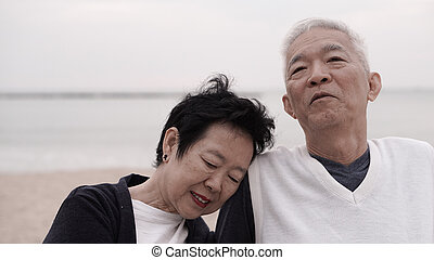 Asian senior couple enjoy their life time together at the sea