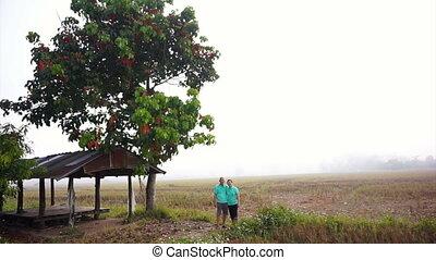 Asian senior couple foggy rice farm