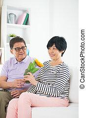 asian senior couple giving flower