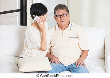 asian senior couple having phone conversation