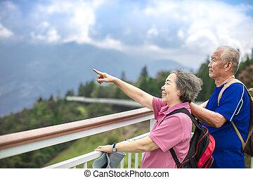 Asian Senior Couple hiking in the mountain park