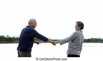 asian senior couple holding hand