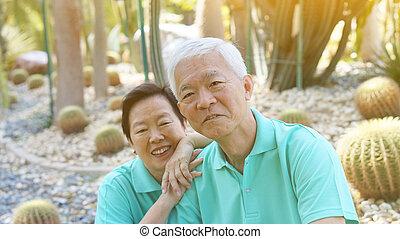 Asian senior couple in Cactus garden