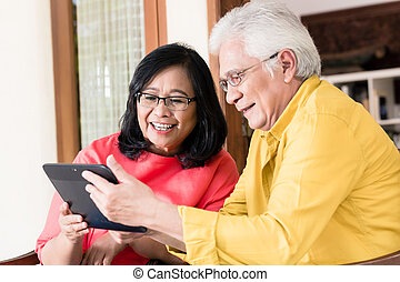 Asian senior couple in love smiling while holding tablet