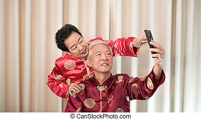 Asian senior couple selfie for Chinese New Year message