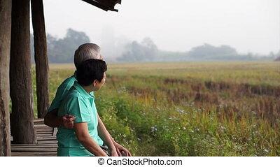 Asian senior couple sit in rice fie