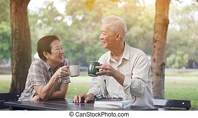 Asian senior couple start morning coffee in park, optimistic...