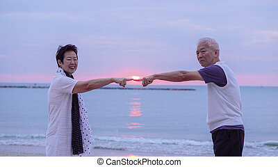 Asian senior couple together at sunrise beach. New year, new chapter concept