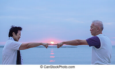 Asian senior couple together at sunrise beach