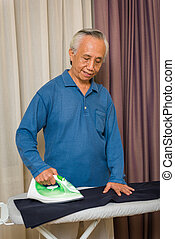Asian senior ironing clothes
