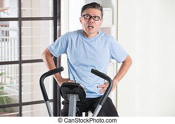 asian senior male panting heavily on exercise bike