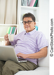 asian Senior Man Reading With Drink At Home
