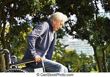 asian senior man trying to stand up from wheel chair
