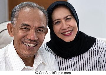 asian senior muslim couple looking at camera