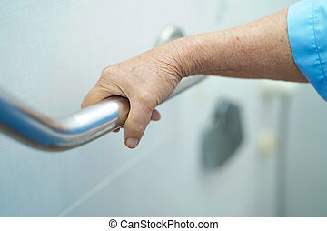 Asian senior or elderly old lady woman patient use toilet bathroom handle security in nursing hospital ward : healthy strong medical concept.