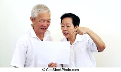 Asian senior couple look at the white sign together. Surprise and happy with the deal on blank white sign