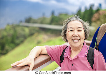 Asian Senior woman hiking in the mountain park