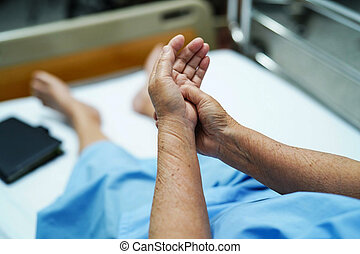 Asian senior woman patient pain her hand in hospital.