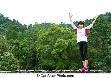 Asian senior woman raise up hand in park